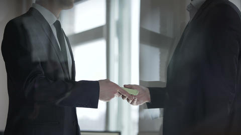 Businessman giving his partner cash, profit from successful business deal Live Action