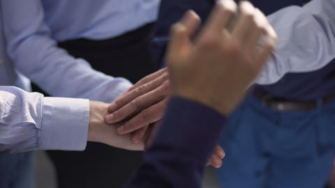 Businesspeople putting their hands on top of each other, team building support Footage