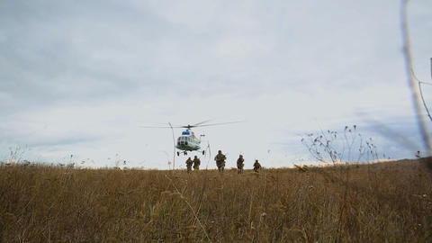 Helicopter flies over soldiers on battlefield Live Action