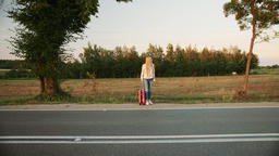 Young lady hitchhiking on countryside road Live Action