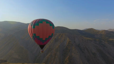 Panoramic view of hot air balloon flying across the sky in mountain landscape Footage