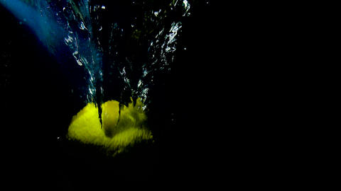 Lush yellow lemon fall in water at black background Slow motion video Footage