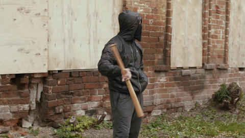 Aggressive bandit in black mask and hood ganging with baseball bat outdoors Live Action