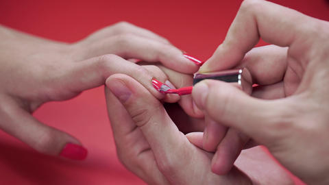 Manicurist paints client's nails with beige tint nail polish on the red ビデオ