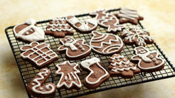 Fresh baked Christmas shaped gingerbread cookies placed on steel grill Footage