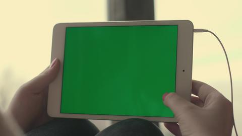 Girl holding a tablet with a green screen Photo