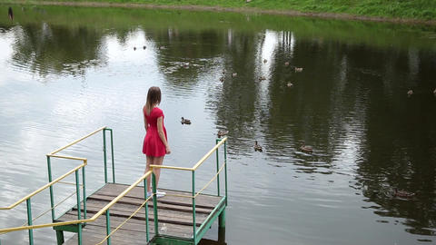 A very beautiful girl in a red dress is standing on a pier near a small lake Footage