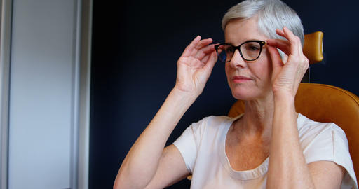 Senior woman adjusting eyeglasses in clinic 4k Live Action