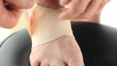Man wraps foot in elastic bandage Footage