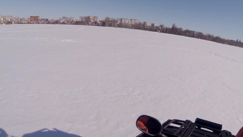 Two guys ride a snowmobile on a frozen lake. Shadows of the guys in the snow Footage