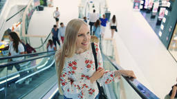 Young blonde woman riding on escalator. Amazed woman in shopping center. Young Live Action