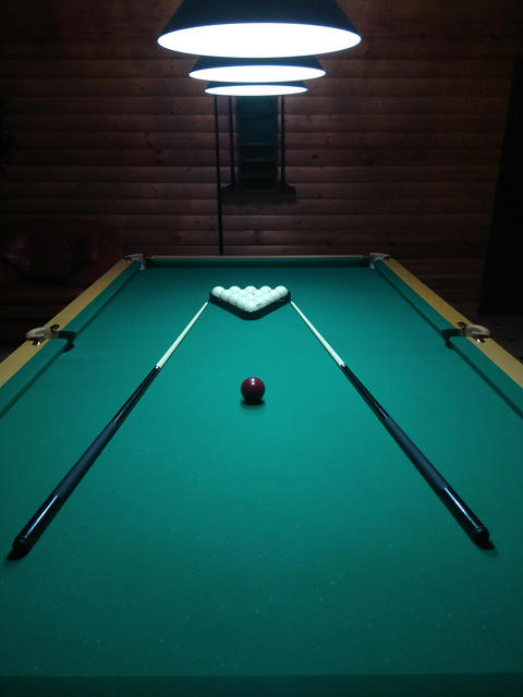 A billiard table has several layers and a cue Photo