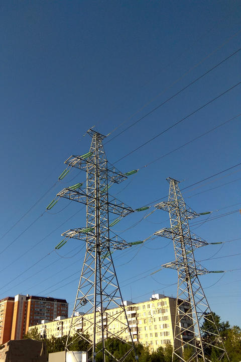 Electric pillars in a big city on the background of a blue sky Photo