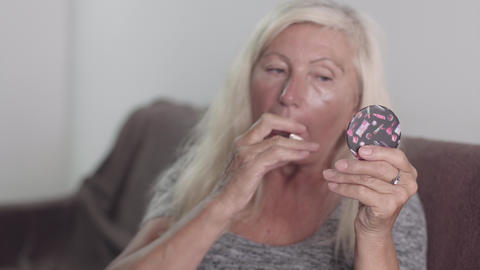 Old Grandmother using the small pocket mirror to use lipstick makeup . Retired Live Action