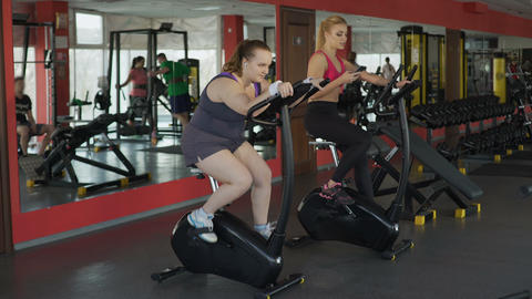 Plump woman working hard at stationary bike to achieve results, fitness, sport Footage