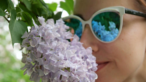 Girl in sunglasses sniffs lilac close up Footage