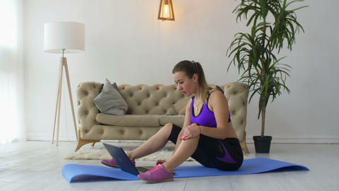 Fit woman watching online video with exercises on laptop Footage
