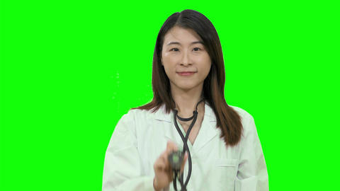 Asian female doctor holding sthethoscope out up on Green Screen Live影片