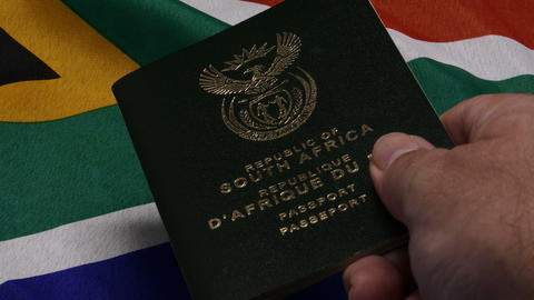 Hand passing RSA passport on RSA flag Live Action
