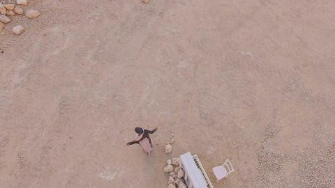 Surreal story- girl near the white piano in the desert against the background of Footage