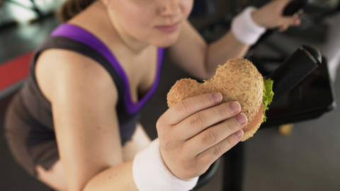 Fat woman riding stationary bike and eating tasty burger in gym, unhealthy diet Live Action