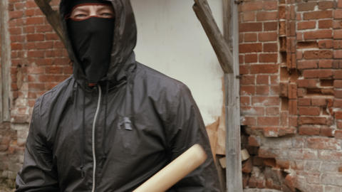 Angry hooligan in black mask and hood making kick to camera Live Action