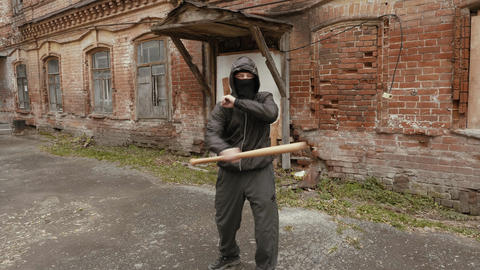 Violent bandit training with baseball bat making kick to camera Live Action