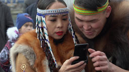 Woman in national clothing indigenous inhabitants reads messages in smartphone GIF