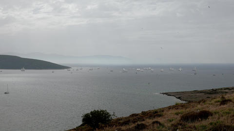 Seascape with sailing boats sail under the white sails passes between two coasts Live Action