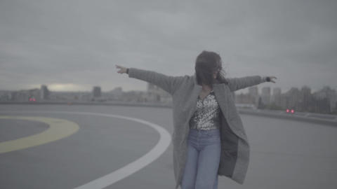 Lovely girl with arms outstretched walks in windy weather. Slow motion, s-log Live Action