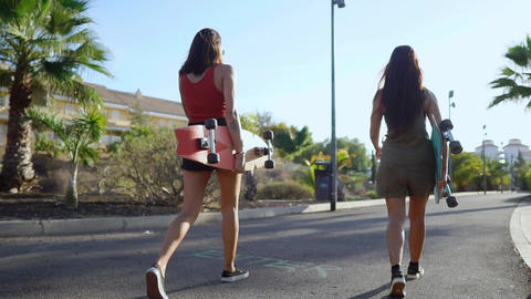 Two girls walking at sunset smiling with boards for skate Board along the path Live Action