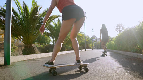 Two girls in skate Park ride along the track in sunlight on longboards looking Live Action