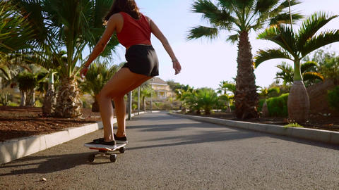 Two girls ride at sunset smiling with boards for skate Board along the path in Live Action