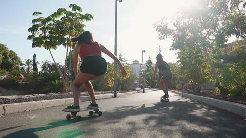 Summer on the island of young girls on longboard rides in short shorts on the Live Action