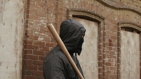 Street hooligan in black mask with baseball bat on criminal street district Live Action