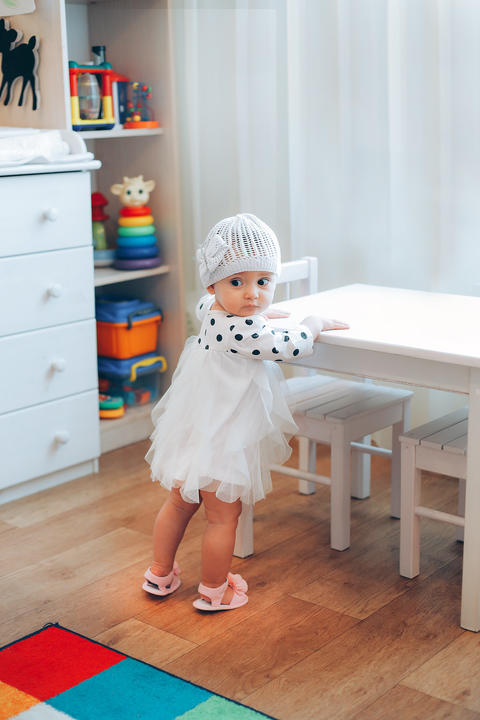 A little girl standing near a white table in a dress with black polka dots フォト