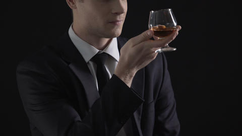 Young successful businessman drinking cognac glass, celebrating successful deal Footage