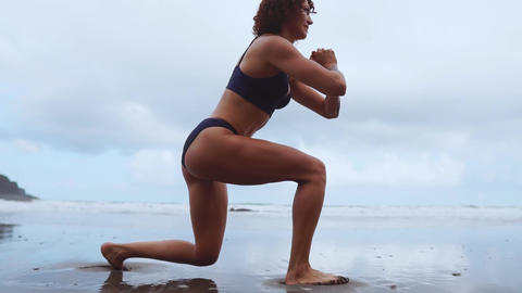 Walking on bent legs along the ocean training the endurance of the leg muscles Live Action