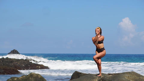 Young girl in bikini balancing stands on one leg doing yoga standing on a rock Live Action