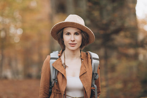 Portrait woman traveler with backpack looking at amazing forest, travel concept Photo
