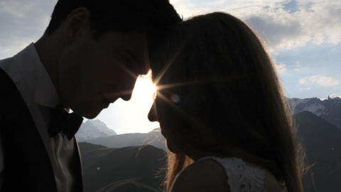 Newlyweds in love kiss in the rays of the setting sun high in the mountains Live Action