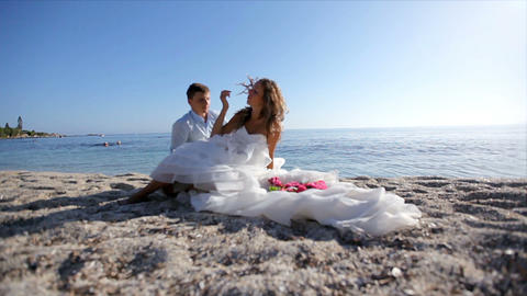 Surrealism. Bride in a gorgeous dress with the groom are on the sand by the sea Footage