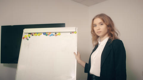 Smiling business woman using flipchart for work with business project in office Live Action