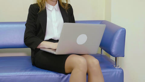 Business woman using notebook pc for work sitting on sofa in business office Live Action