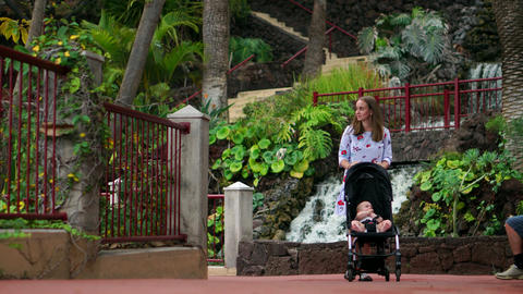 Mother and child walk around the waterfall during a tour of the Canary Islands Live Action