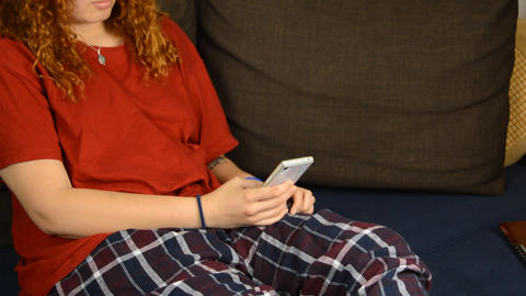 Young Adult Girl Plays With Her Smartphone in Pajamas Stock Video Footage