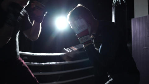 Silhouette of two men who are sparred on a ring at night Live Action