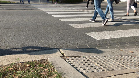 Citizens cross road by zebra crossing near public transport Live Action