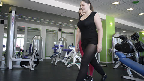 Woman does exercise under supervision of trainer Footage