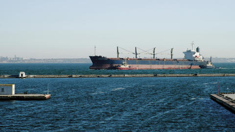 Cargo ship sailing on sea. Merchant ship swinging on waves. Clear day at seaport Footage